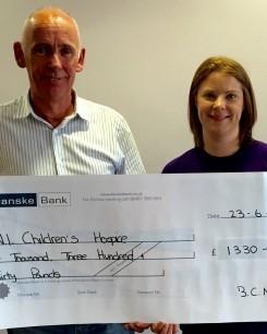 Paul McQuillan, Armagh City , Banbridge and Craigavon Borough Council, presenting a cheque to NI Children's Hospice.